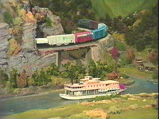 Another train emerges from one of the many tunnels and passes a boat churning down a river.