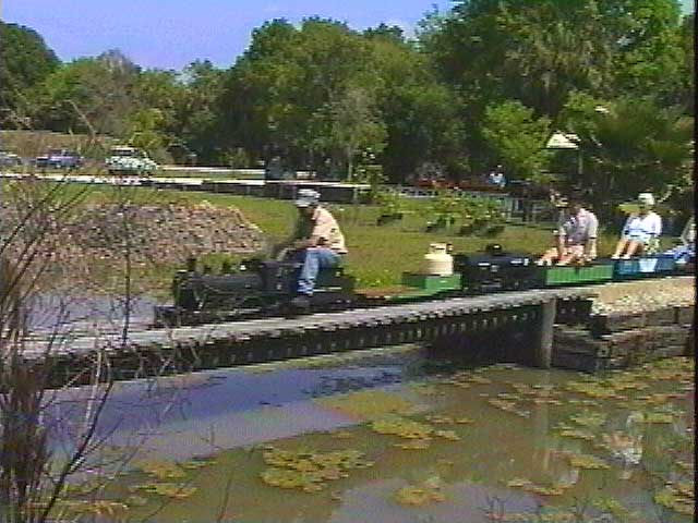 A steam engine pulls a train full of visitors across a long bridge over a lake on this scenic layout.