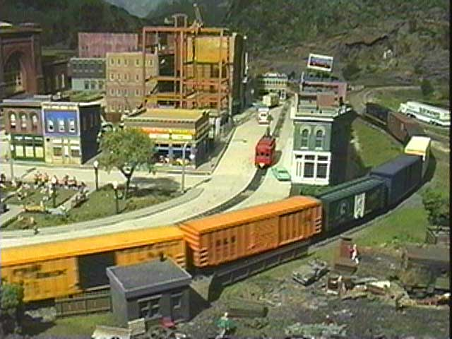 Here's an example of the highly-detailed scenery; a train passes along the edge of a city.
